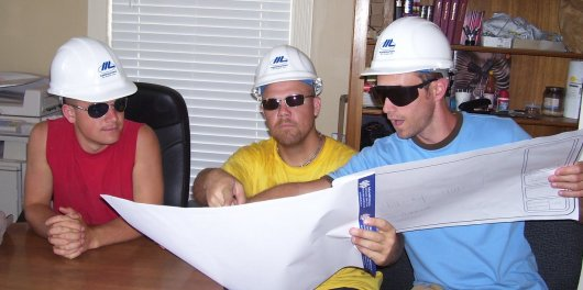 Andrew, Joel, and Doug study a set of building plans and show off their cool hats