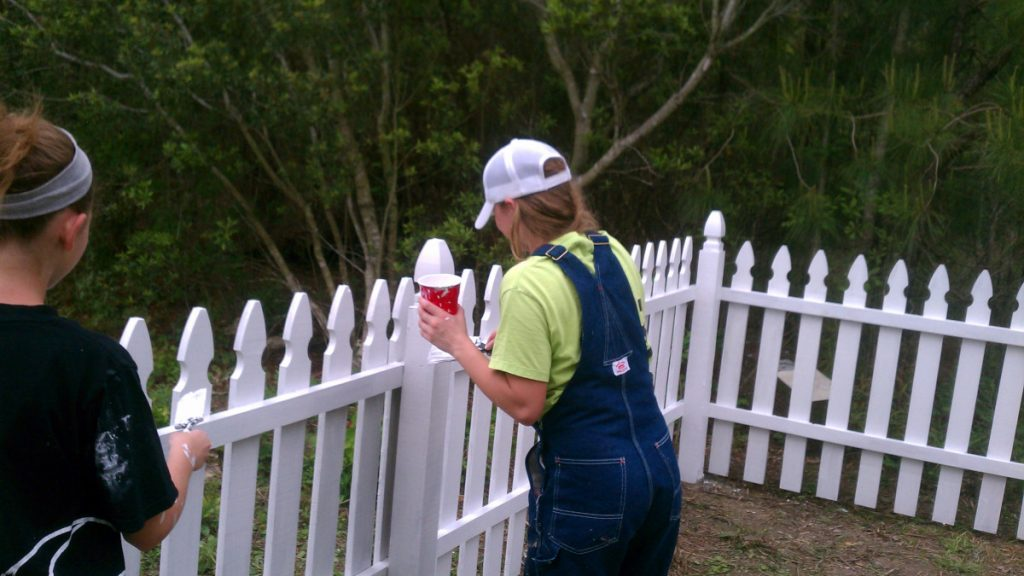 Girl painting fence on mission trip